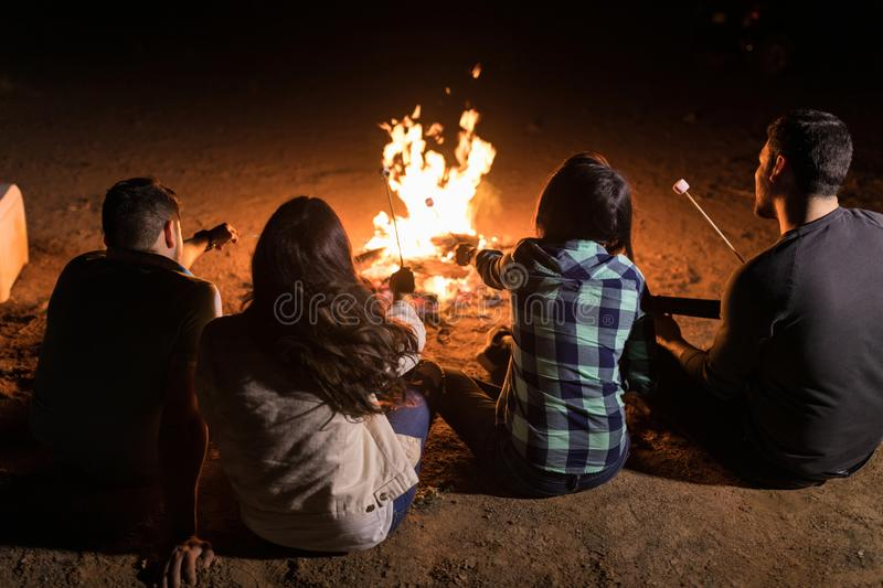 Group Of Friends Sitting Around Bonfire royalty free stock photos