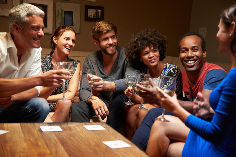 Group of friends sitting around a table at house party stock images