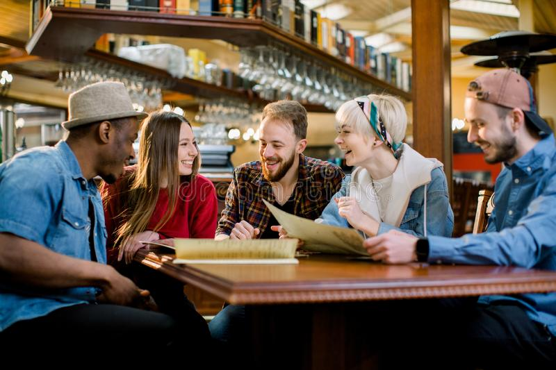 Group of friends sitting cafe. Happy youg people having fun together, sitting on couch and choose meals from the menu. royalty free stock photos