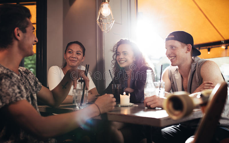 Group of friends sitting in cafe and having fun stock images