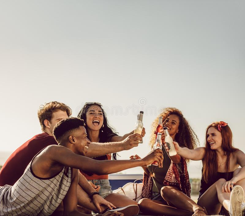 Partying outdoors with beers. Group of friends sitting outdoors and toasting drinks. Cheerful young people having beers on a summer day royalty free stock photo