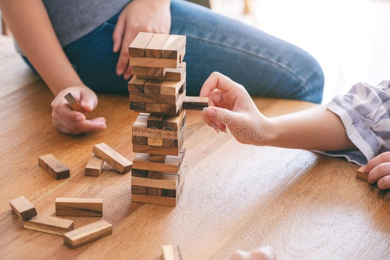 Friends sitting and playing Tumble tower wooden block game together with feeling happy. Group of friends sitting and playing Tumble tower wooden block game stock photography
