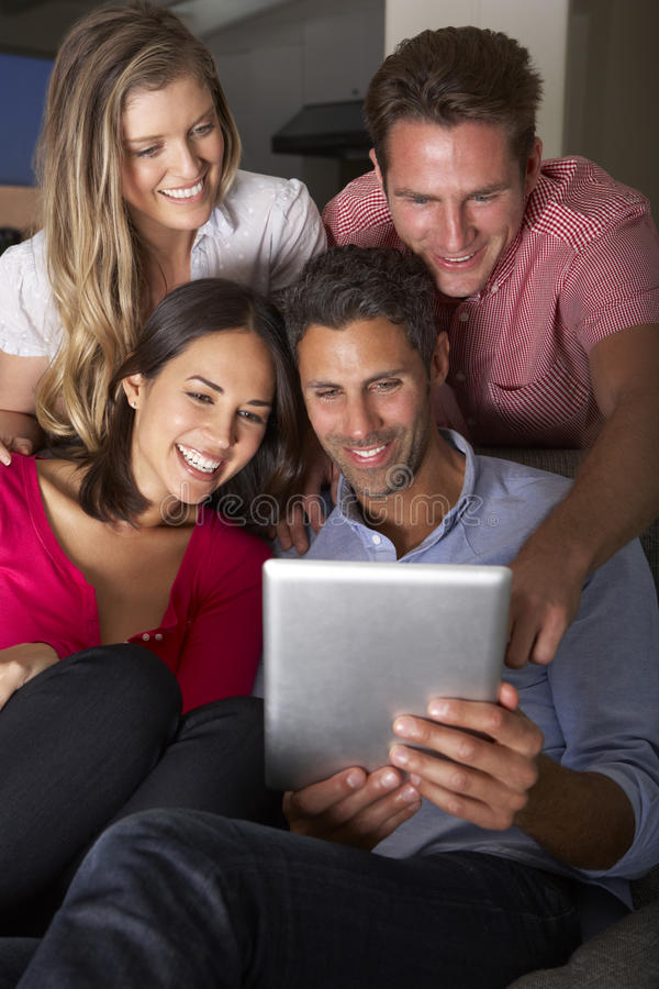 Group Of Friends Sitting On Sofa Looking At Digital Tablet stock images