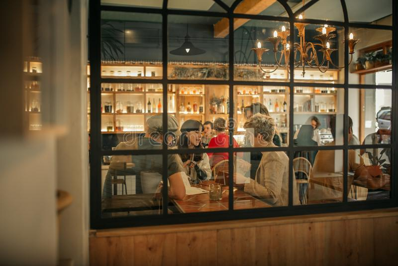 Smiling friends ordering drinks inside of a trendy bar. Group of friends sitting together at a table by windows inside of a trendy bar ordering drinks from a royalty free stock images