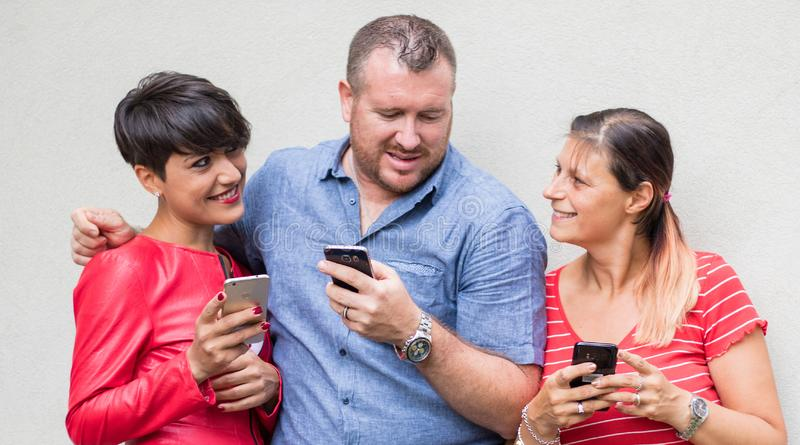 Group of friends smiling and looking the smartphone stock photography