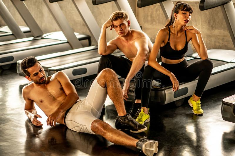 Group of friends sport people tired taking a break from running or exercise sitting on treadmill machine in fitness gym. over. Training . heat , hot temperature stock image