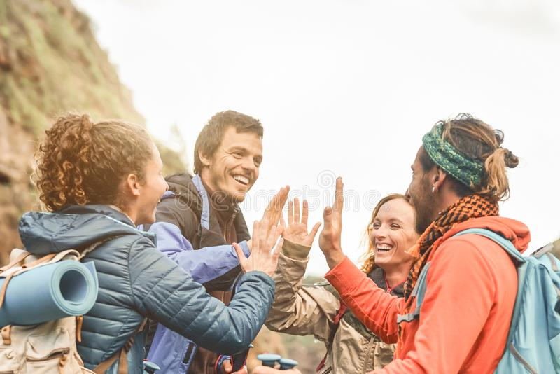 Group of friends stacking hands while doing trekking excursion on mountain - Young tourists having fun exploring the wild nature stock images