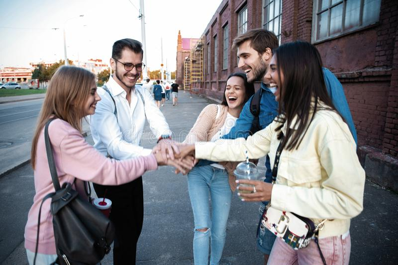 Group of friends stacking hands outdoor - Happy young people having fun joining and celebrating together stock photo