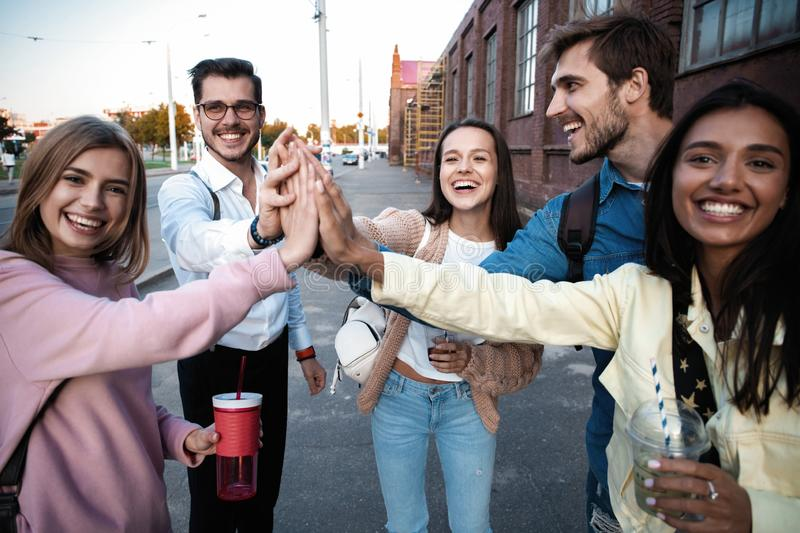 Group of friends stacking hands outdoor - Happy young people having fun joining and celebrating together royalty free stock photo