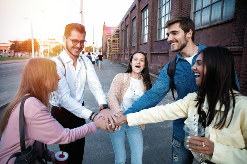 Group of friends stacking hands outdoor - Happy young people having fun joining and celebrating together royalty free stock photos