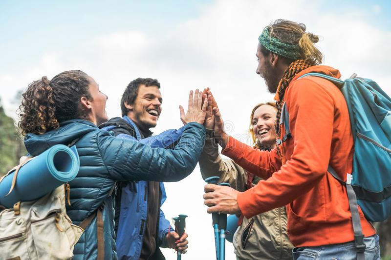 Group of friends stacking hands on peak of mountain - Young tourists trekking and exploring the wild nature royalty free stock photo