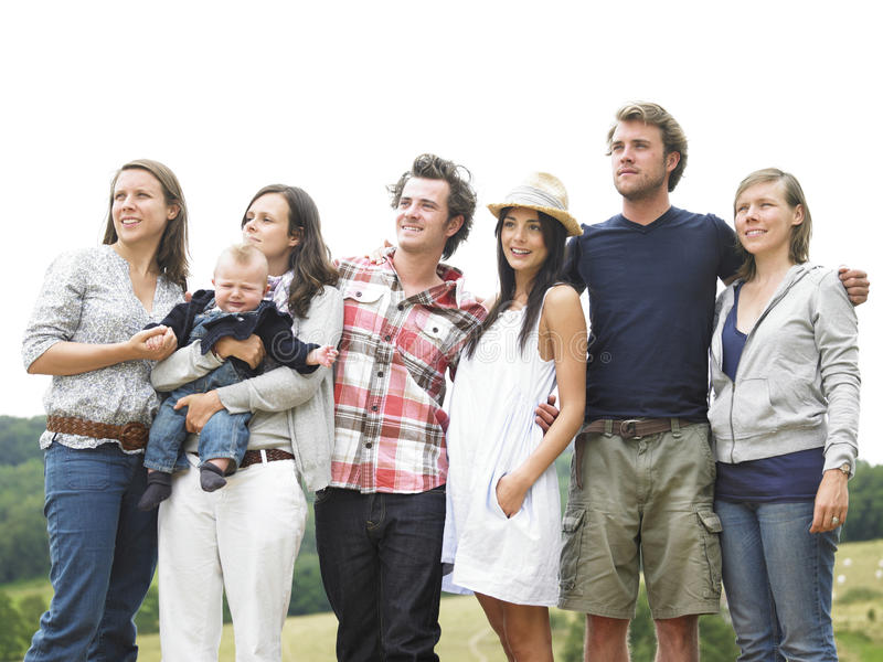 Group of Friends Standing Outdoors. Group of young people, with one woman holding a baby, standing outdoors and looking off into the distance. Horizontal royalty free stock photography
