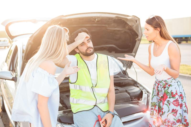 Group of friends stranded on the parking lot by a broken car during road trip royalty free stock photos