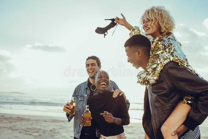 Group of friends on summer vacation. Group of multi-ethnic friends enjoying their holidays on the beach. Two cheerful couples on summer vacation royalty free stock photography