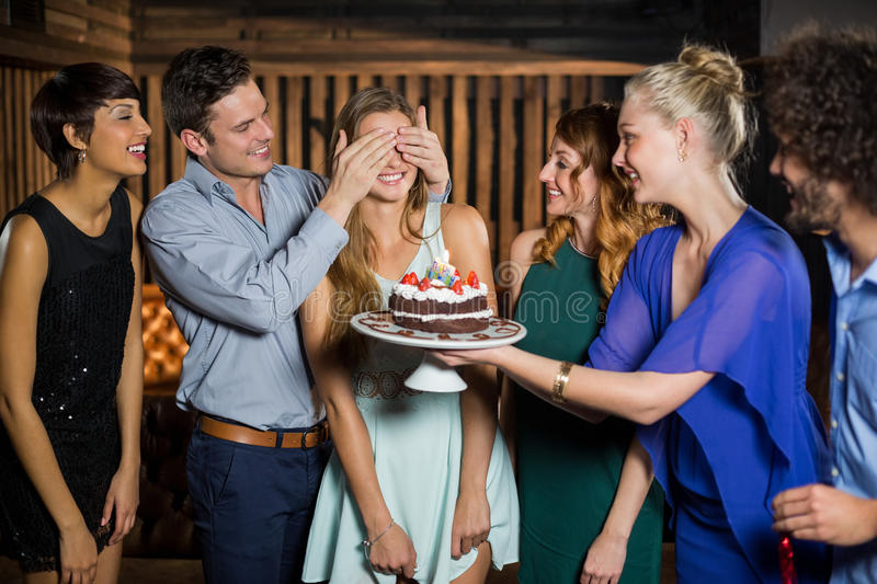 Group of friends surprising a woman with birthday cake. Group of friends surprising a women with birthday cake in bar royalty free stock photo