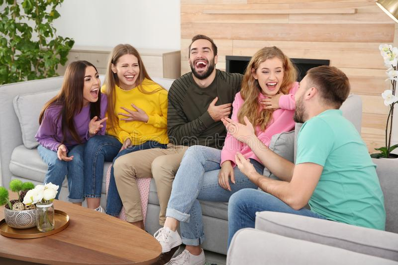 Group of friends telling jokes and laughing. In living room stock photos