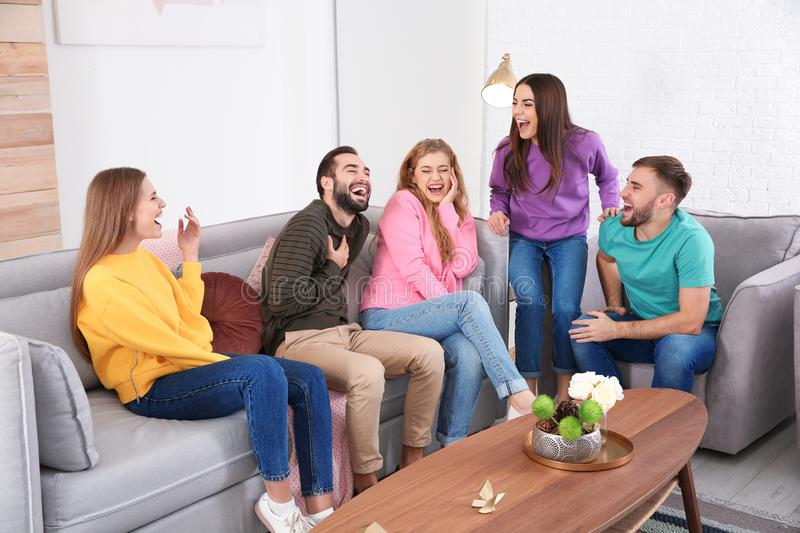 Group of friends telling jokes and laughing. In living room royalty free stock photos
