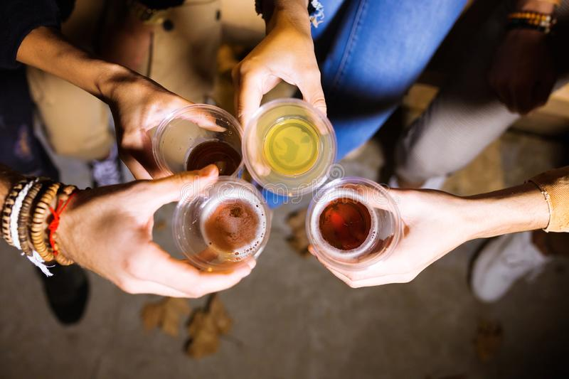 Group of friends toasting with beer in eat market in the street. Close-up of group of friends toasting with beer in eat market in the street royalty free stock image