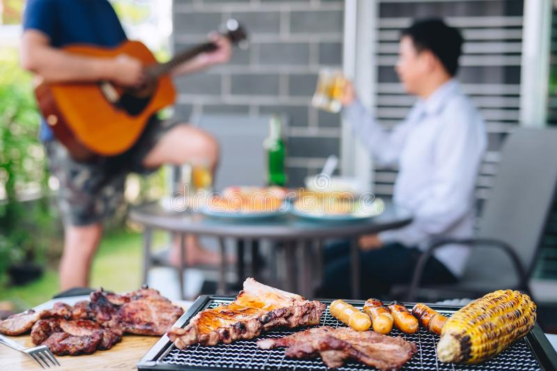 Group of friends Two young man enjoying grilled meat and play guitar with raise a glass of beer to celebrate the holiday festival stock images