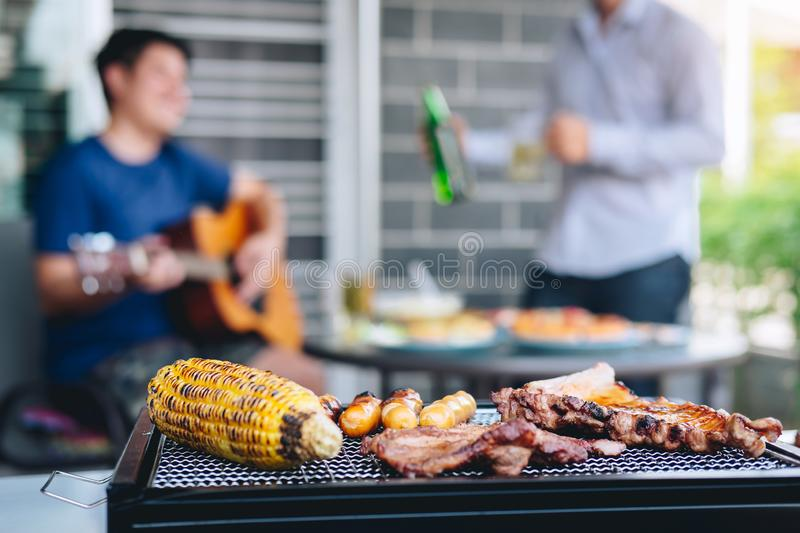 Group of friends Two young man enjoying grilled meat and play guitar with raise a glass of beer to celebrate the holiday festival. Happy drinking beer outdoors stock photography