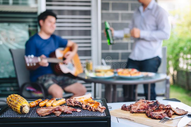 Group of friends Two young man enjoying grilled meat and play guitar with raise a glass of beer to celebrate the holiday festival. Happy drinking beer outdoors royalty free stock images