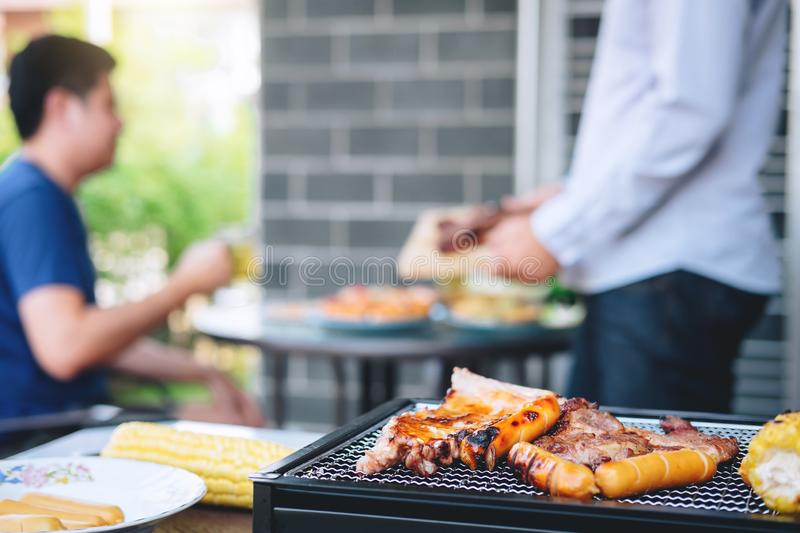 Group of friends Two young man enjoying grilled meat and raise a glass of beer to celebrate the holiday festival happy drinking. Group of friends Two young men royalty free stock photo
