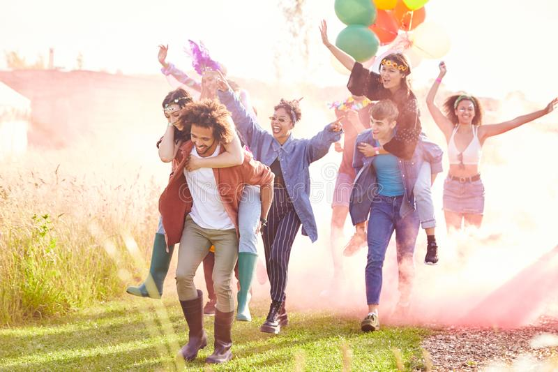 Group Of Friends Walking Back To Tent After Outdoor Music Festival With Balloons And Smoke Flare stock photography