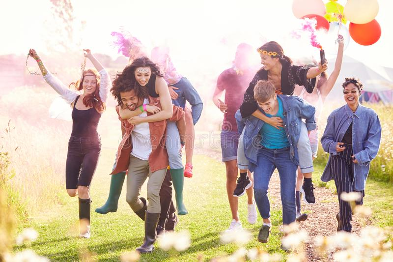 Group Of Friends Walking Back To Tent After Outdoor Music Festival With Balloons And Smoke Flare royalty free stock photo