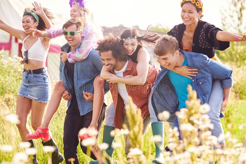 Group Of Friends Walking Back To Tent After Outdoor Music Festival With Men Giving Women Piggybacks stock image