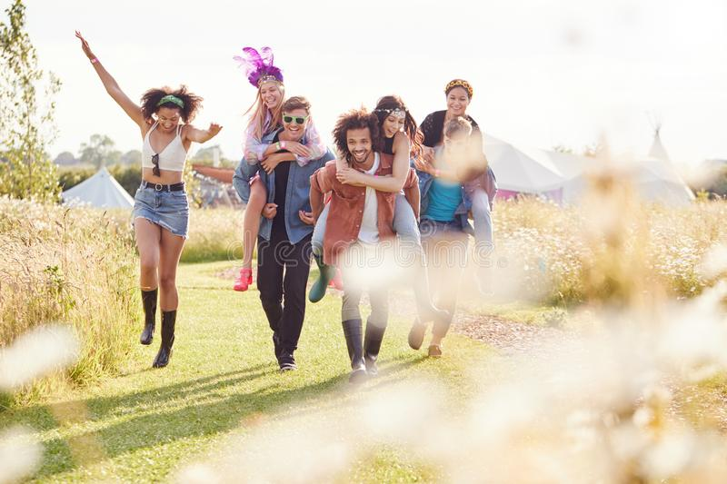 Group Of Friends Walking Back To Tent After Outdoor Music Festival With Men Giving Women Piggybacks stock photography