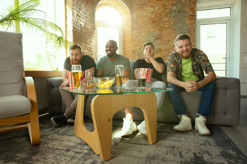 Group of friends watching football or soccer game on TV at home stock image