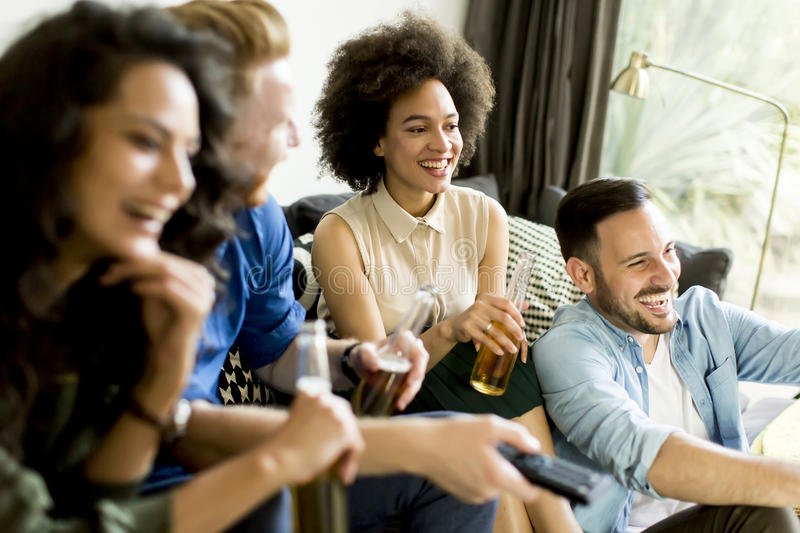 Group of friends watching TV, drinking cider and having fun. Group of friends watching TV , drinking cider and having fun in the room stock photo