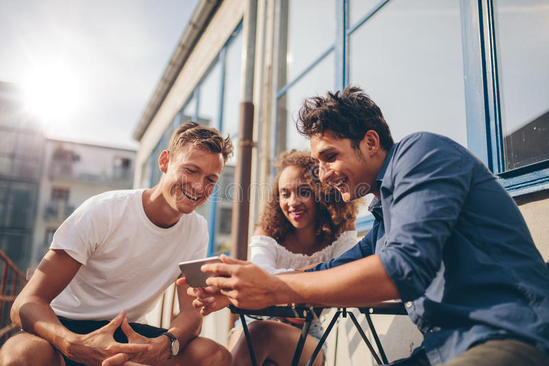 Group of friends watching video on smartphone stock photography