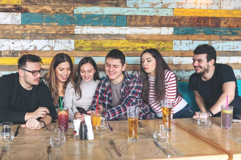 Group of friends watching videos on smartphone at pub restaurant royalty free stock images
