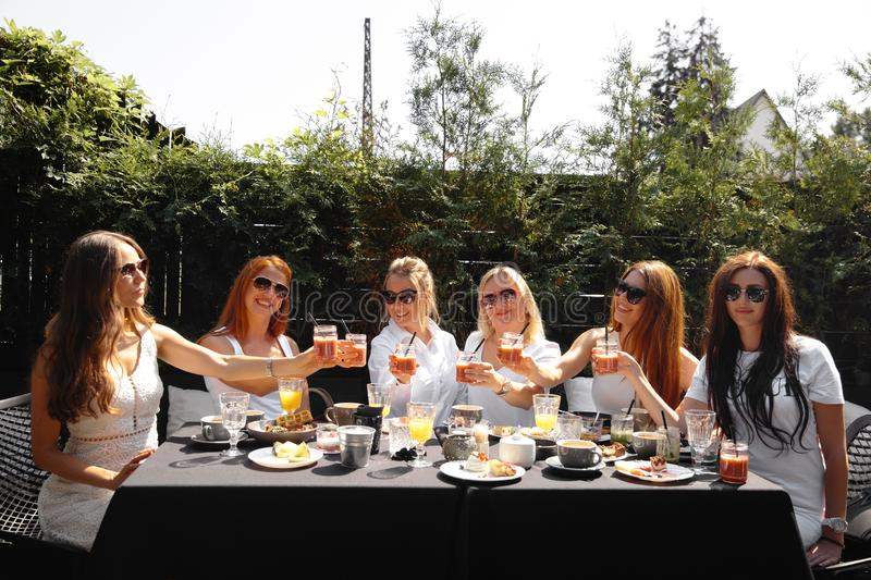 Group of friends in white having breakfast in garden at table with food and communicating, laughting concept. Summer morning gathering of ladies in their 30s royalty free stock photo