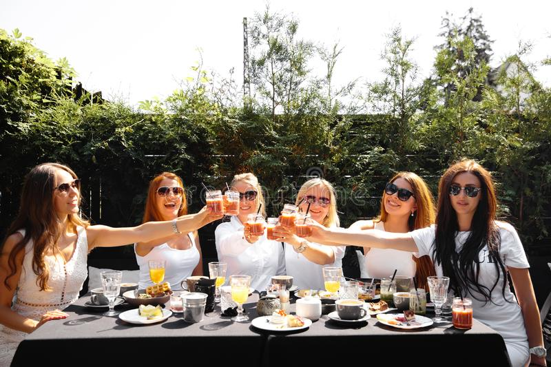 Group of friends in white having breakfast in garden at table with food and communicating, laughting concept. Summer morning gathering of ladies in their 30s stock photos