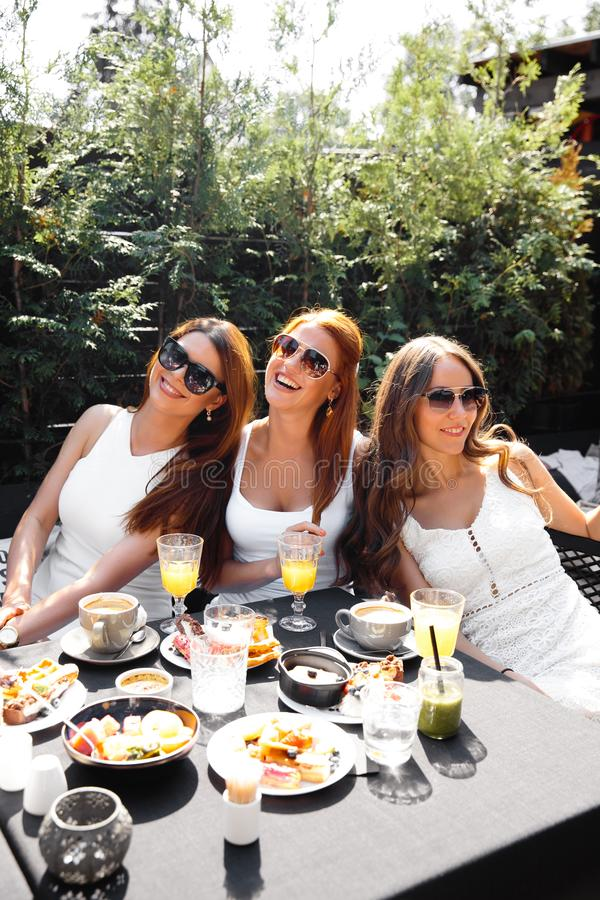 Group of friends in white having breakfast in garden at table with food and communicating, laughting concept. Summer morning gathering of ladies in their 30s royalty free stock photography