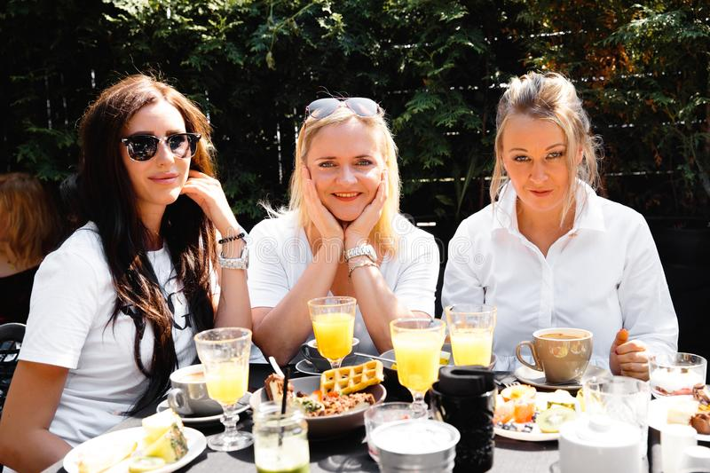 Group of friends in white having breakfast in garden at table with food and communicating, laughting concept. Summer morning gathering of ladies in their 30s stock photo