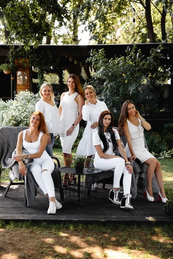 Group of friends in white preparing to pose for a photoshoot in a cafe garden in the Summer morning royalty free stock photography