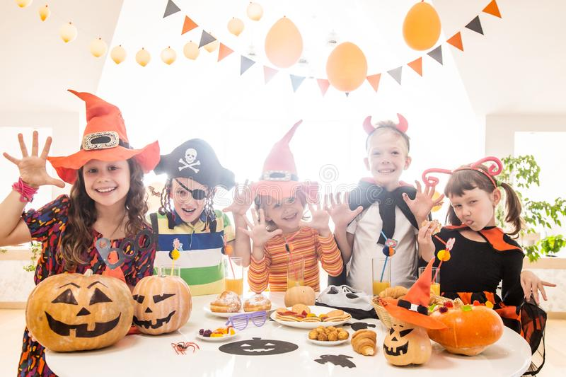Kids in Halloween party. Group of funny children in costume celebrate together a halloween party stock photo