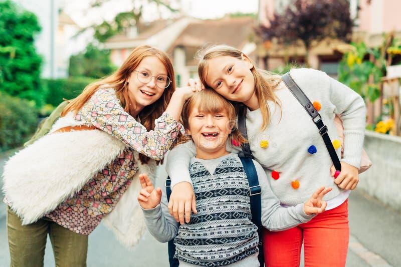 Group of 3 funny kids with backpacks, 2 schoolgirls and one preschooler stock photos