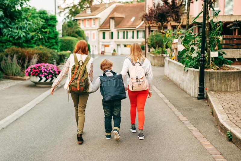 Group of 3 funny kids with backpacks, 2 schoolgirls and one preschooler stock photography