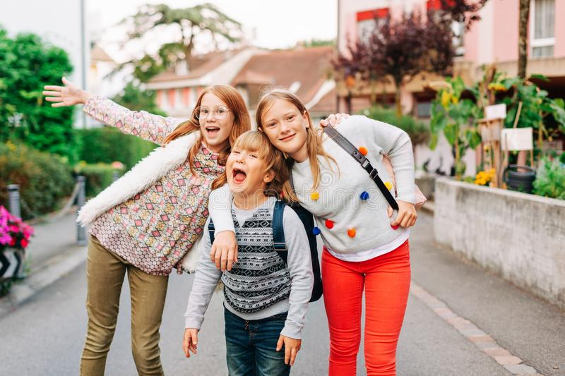 Group of 3 funny kids with backpacks, 2 schoolgirls and one preschooler royalty free stock images