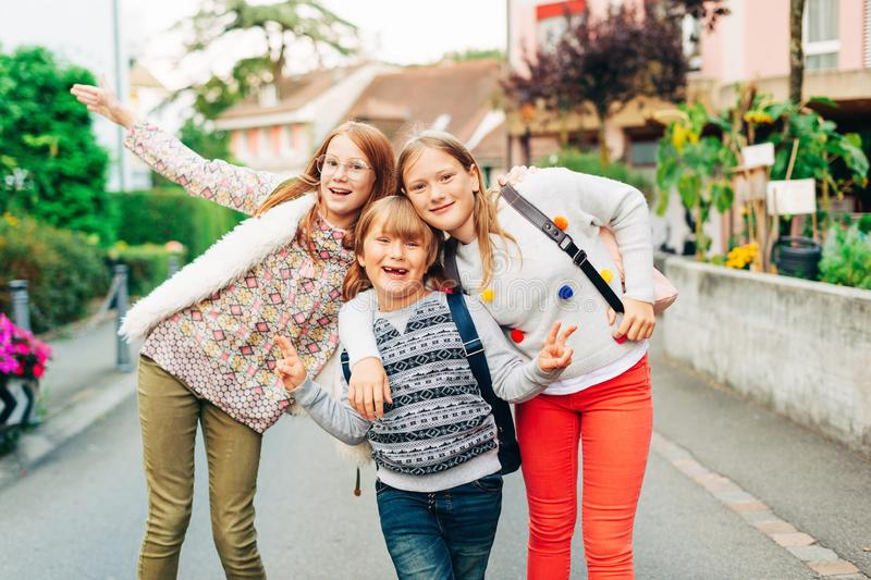 Group of 3 funny kids with backpacks, 2 schoolgirls and one preschooler royalty free stock photos