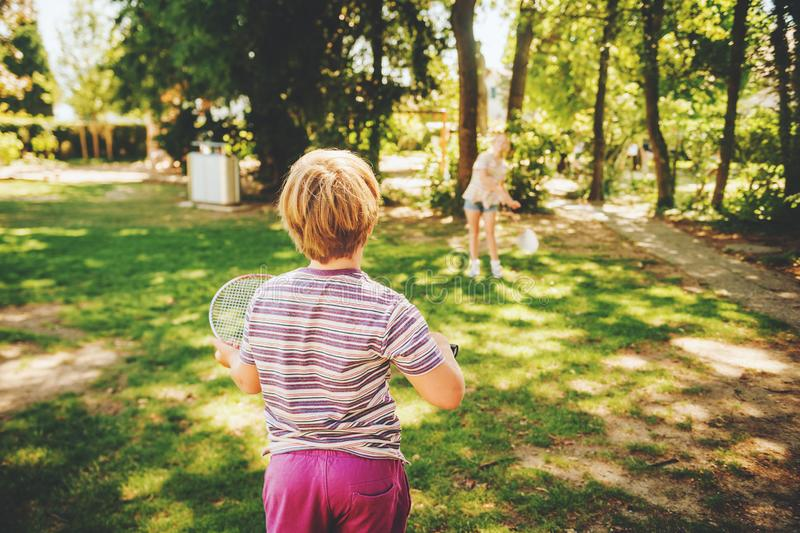 Group of 2 funny kids friends playing badminton in summer park stock image