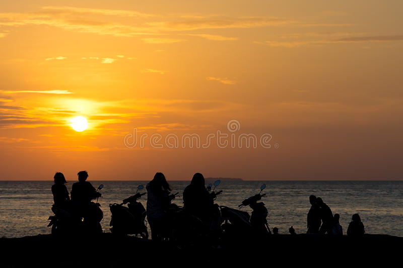 Group Gang of Teenagers Young Adults watch a beach side sun set. On their scooters stock photography