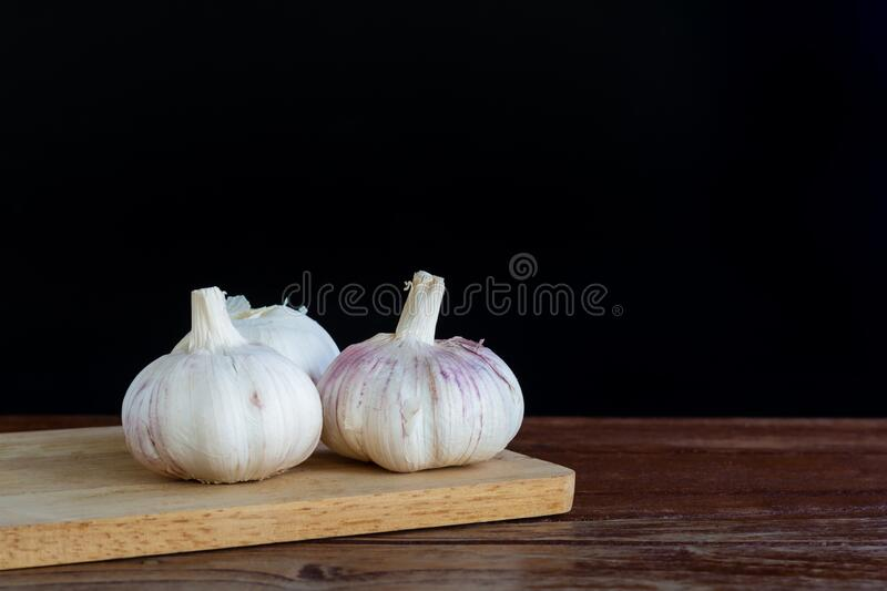 Garlic on chopping board and wooden table with black background. Copy space for your text. Group of garlic on chopping board and wooden table with black stock images