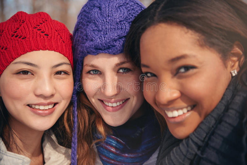 Group of girl friends enjoying taking selfies in the snow in winter. Group of millenial young female adult friends enjoying wintertime and in a snow filled park stock photo