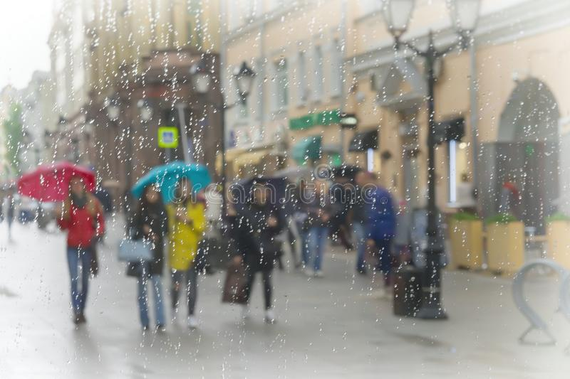 Group of girls in bright clothes under umbrellas. Rainy day in city, raindrops on glass of window stock images