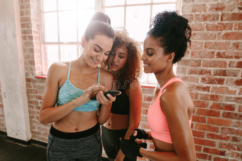 Group of girls in fitness class looking at smartphone royalty free stock photo
